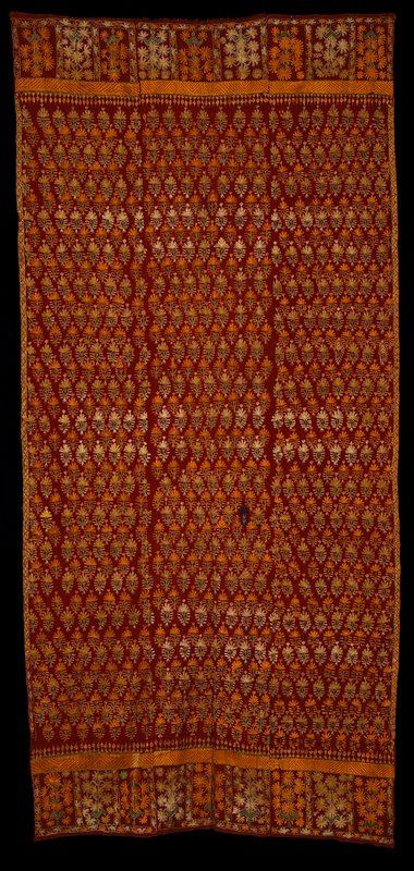 three panels hand stitched together; solid silk floral embroidered pattern in horizontal rows in orange, yellow and green on rust, one random purple; top and bottom borders have smaller floral pattern