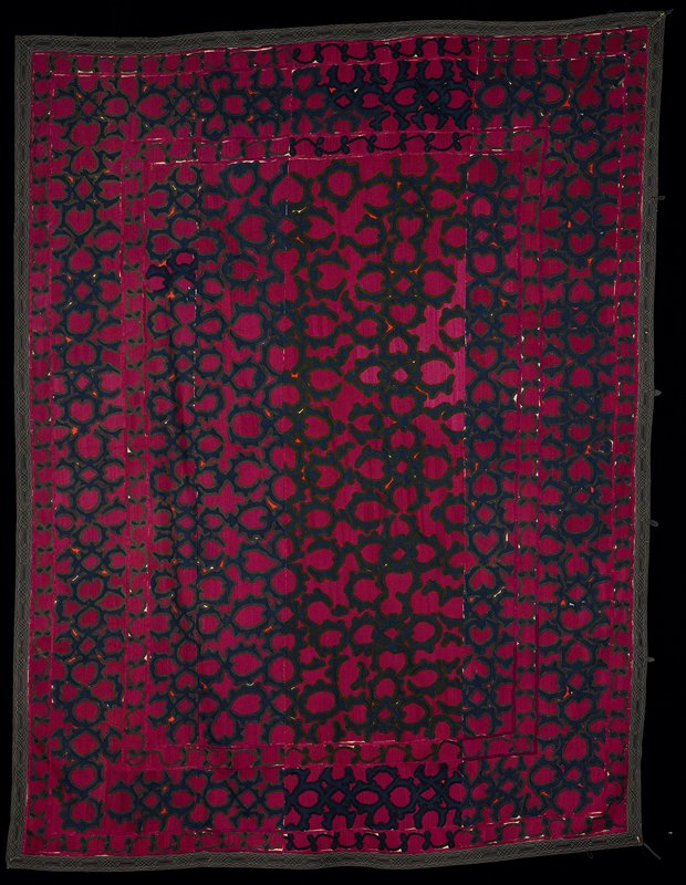 """four cotton panels sewn together entirely embroidered with silk; one floral pattern repeated; dark red, purple, green, blue, black and orange motif in borders; two different embroidery stitches; 2"""" black binder gadroon all around the piece: machine stitched motifs; lining at back with """"faux"""" Ikat- yellow, red and pale yellow cotton"""