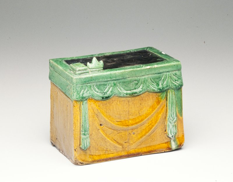 Tomb furniture; table with 2 objects on top at proper right front corner; center of table glazed black with edges and objects glazed green; front and sides of table draped with green swags and valances and tan drapery; open back