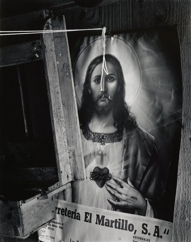 poster with image of Jesus, text at bottom; wood structure at left covers part of image; loops of string hanging and extending from nail at top of poster
