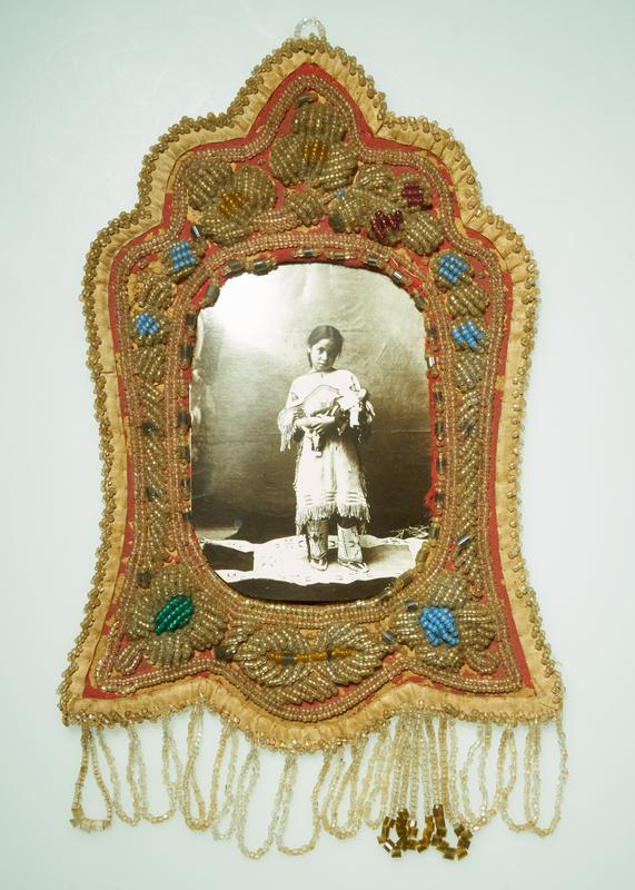roughly bell-shaped; red and cream on front; red on back; raised floral motif beading in predominately clear beads; clear and olive dangling loops; received with reproduction image of Native American girl with doll