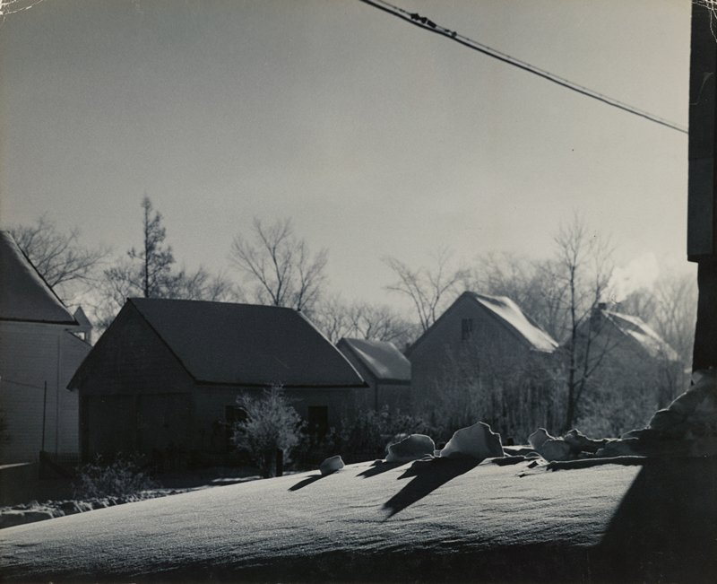 snow drift and snow clumps in foreground; small buildings and bare trees in background