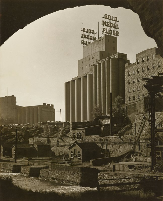 """flour mills with tall silos in background; """"GOLD MEDAL FLOUR"""" sign; smaller buildings by river in foreground"""