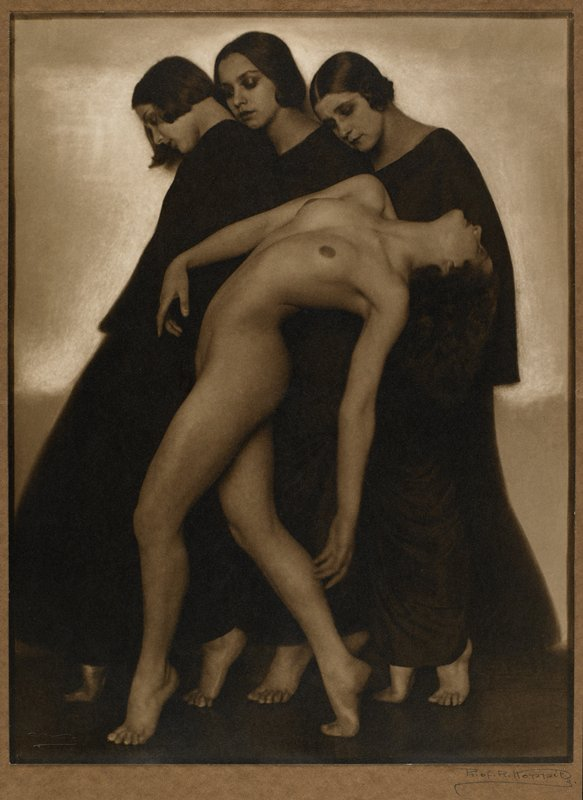 three women wearing dark robes, with bare feet, and standing on tiptoes; nude woman in front of robed women, also on tiptoes, bending backwards, in profile
