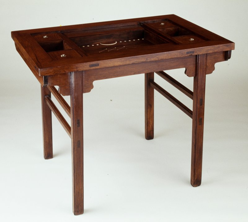 table with removable top; removable two-sided game board inside with ivory circles inlaid on one side; three removable compartments, two with lids, at each short side; another removable gameboard with four short sidewalls and ivory inlay under the two-sided gameboard; two compartments with hinged lids on long sides on inner gameboard