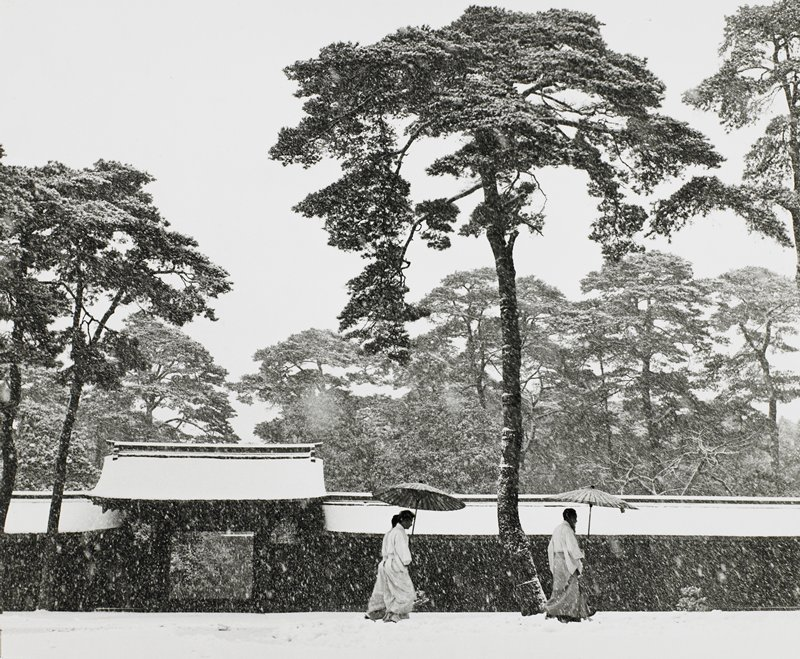 three figure walking in snow, umbrellas raised, in front of temple wall; evergreen trees in middle ground and background