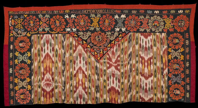 black borders at sides and top, trimmed in rust, with central triangular piece; lower center is red, white, yellow, purple, olive and brown ikat; black areas decorated with curvilinear designs alternating with orange medallions surrounding shooting stars and flowers; medallion on triangle with flower in center; text embroidered at top edge
