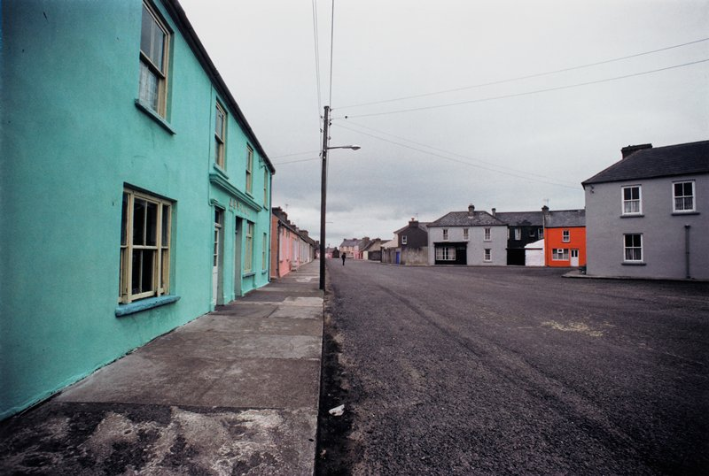 deserted road-one figure standing in road in distance; turquoise building at L; grey, white, black, brown and orange buildings at R; street light pole, electric wires and curb create a vertical line, L of center