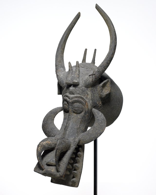 animal's head with squared-off snout; four tusks and six horns; diamond-shaped ears; encrusted patina-only small fragments of pigment remain