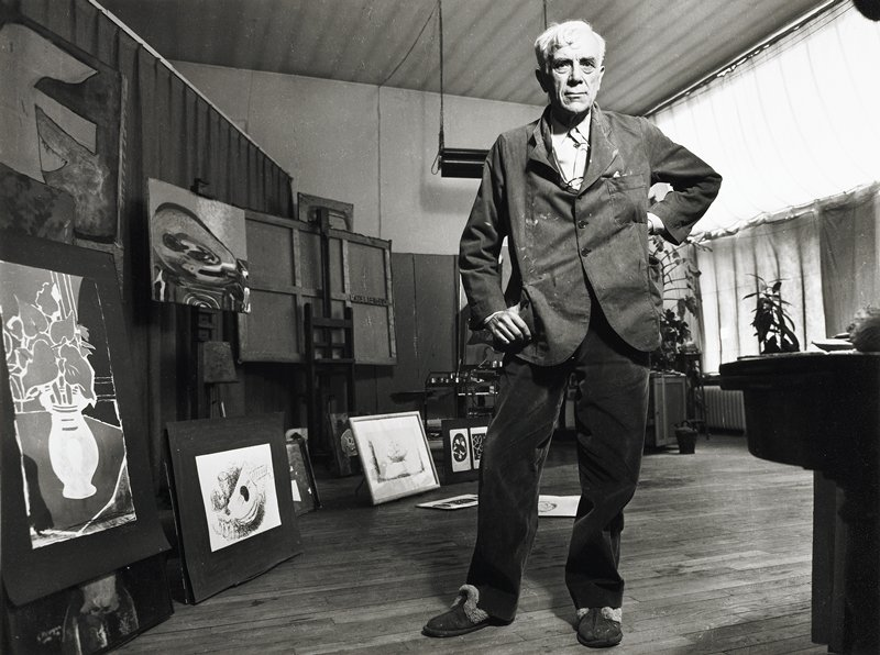 standing man with white hair, wearing a smock, dark pants, slippers and glasses around his neck; various two-dimensional artworks hanging, on easels and leaning up on the floor at L