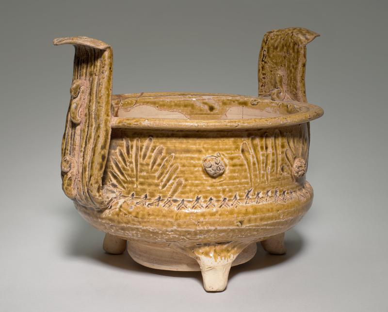 "straight sides; three feet and foot ring; two wide vertical ""handles""; vessel decorated with incised lines and applied ""rosettes""; handles decorated with applied S-shaped elements; tan glaze with greenish tones"