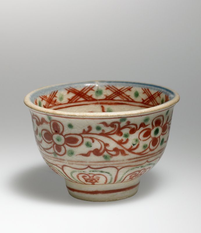 small bowl; ring foot; mouth rim flares slightly outward; white ground; blue, green and red flower and organic motifs with band of X's around interior rim