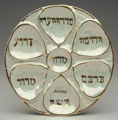 plate with pearly glaze on top, plain white on bottom; compartmentalized floral motif with gilt edging and Hebrew lettering
