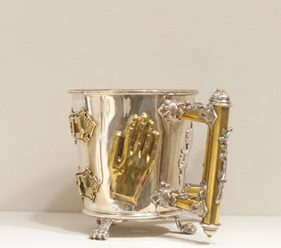 double-handled cup on 3 lion's paw feet; hands on either side of cup in front of handles; 2 heavy applied inscriptions on front; handles decorated with vines and berries; rampant lion with sack on back