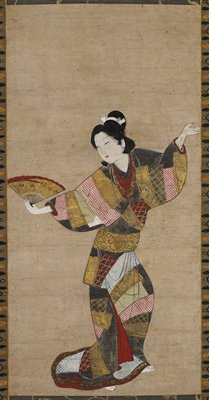 Single female figure dancing. She wears a colorful kimono with a design of colorful fabrics in red, black, gold, and light blue. She holds a gold and red folding fan in her right hand, while her left hand is raised.