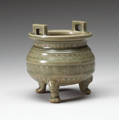 celadon green; three small paw feet with animal heads; two squared-off handles on top rim; four rows of incised geometric designs on body