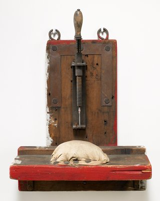 functioning handled screw device with a blade at bottom, pointed toward a cloth-covered, padded area on horizontal board; portions painted red and white
