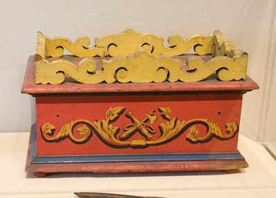 box with knob feet painted red with blue, black and gold decoration; central decoration is three rings, with a crossed axe and staff; three rings and eye on either end