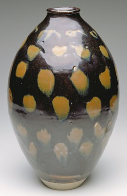 bulging sides from narrow base and narrow shoulder; everted lip; shiny black glaze with iron oxide (brown) dot-like splotches overall and scrolls at shoulder