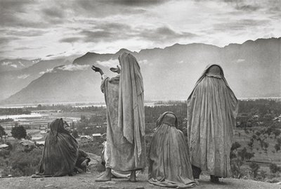 four robed figures in foreground on a plateau overlooking a village; water and mountains in background